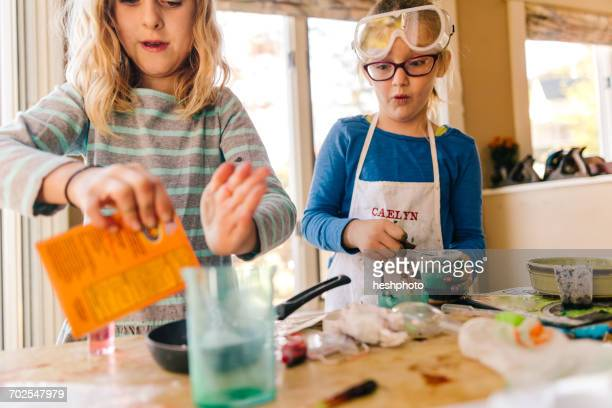 two girls doing science experiment, pouring packet into frying pan - heshphoto stockfoto's en -beelden
