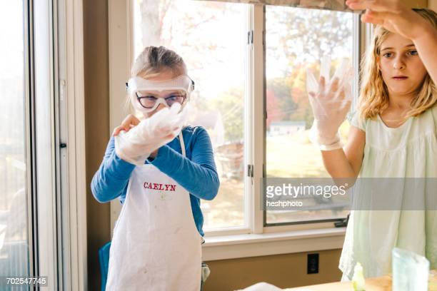 two girls doing science experiment, putting on large latex gloves - heshphoto stockfoto's en -beelden