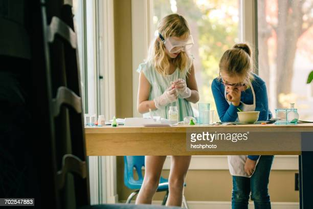 two girls doing science experiment, reading chemistry set instructions - heshphoto stockfoto's en -beelden
