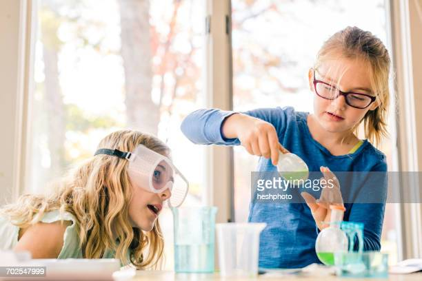 two girls doing science experiment, shaking liquid in flask - heshphoto - fotografias e filmes do acervo