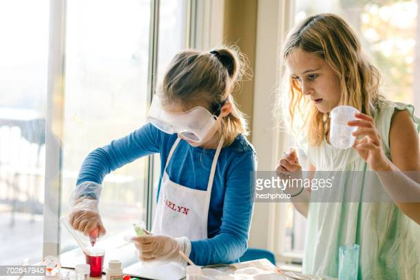 two girls doing science experiment, with red liquid - heshphoto stockfoto's en -beelden
