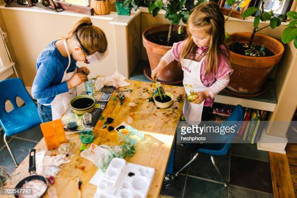 two girls doing science experiments at messy table - heshphoto stockfoto's en -beelden