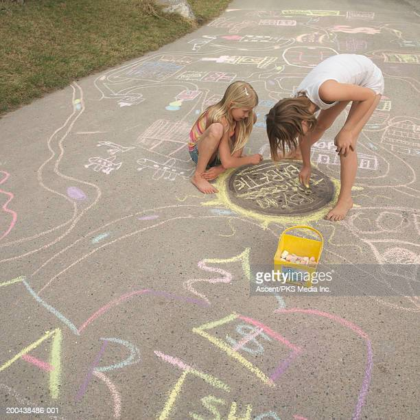 two girls (8-10) drawing on sidewalk with chalk, elevated view - little girls bent over stock photos and pictures