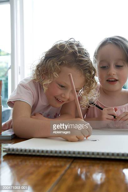 'Two girls (4-6) drawing picture in sketch pad on table, smiling'