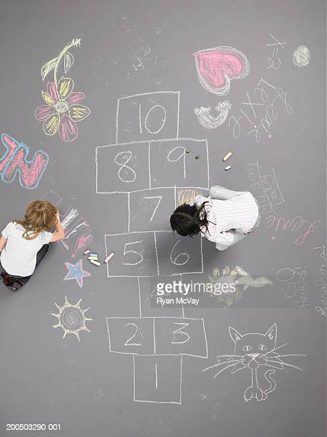 Two girls (8-10) drawing with chalk beside hopscotch squares