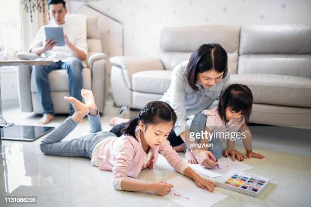 two girls drawing with parents at home - family with two children stock pictures, royalty-free photos & images