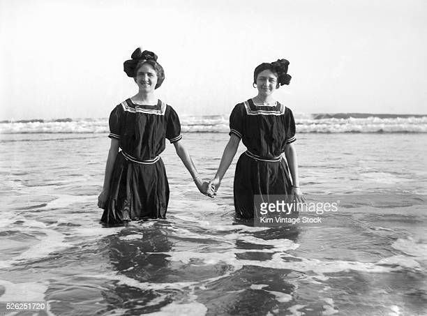 Two girls dressed in period swimwear stand together for a portrait in the Pacific Ocean on the coast of California.