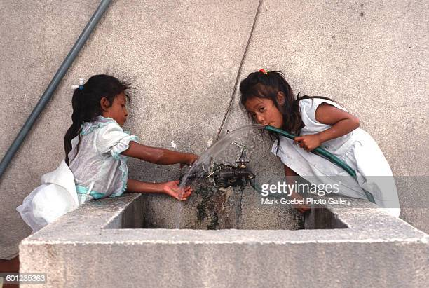 Two girls drink from a water hose, Juarez, Mexico, late 1980s. Both wear white dresses.