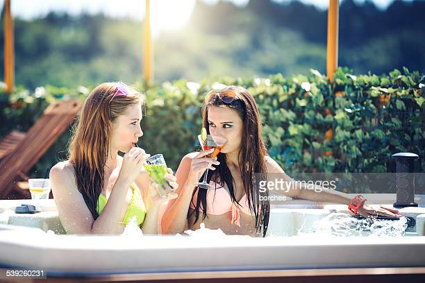 Two Girls Drinking Cocktail In hot tub