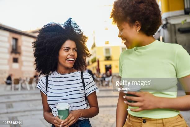 two girls drinking coffee and having fun outdoors - questão da mulher imagens e fotografias de stock