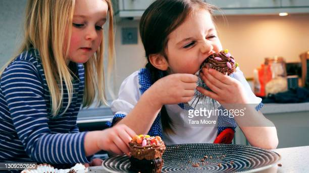 two girls eating cupcakes - childhood stock pictures, royalty-free photos & images