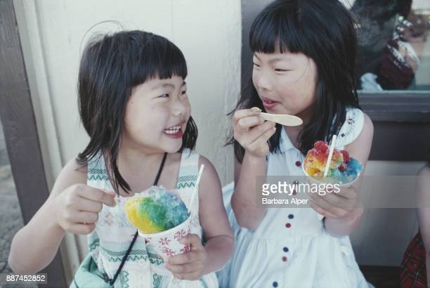 Two girls eating shave ice at Matusmoto's in Haleiwa Oahu Hawaii US March 2000