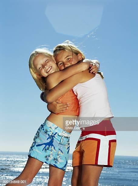 two girls (8-10) embracing on beach, portrait - girls with short skirts - fotografias e filmes do acervo