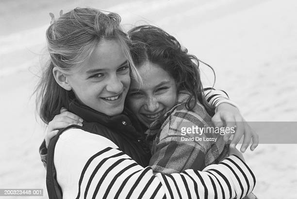Two girls (10-12) embracing,close-up (B&W)
