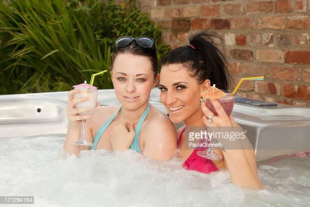 Due ragazze goditi un cocktail in una vasca idromassaggio