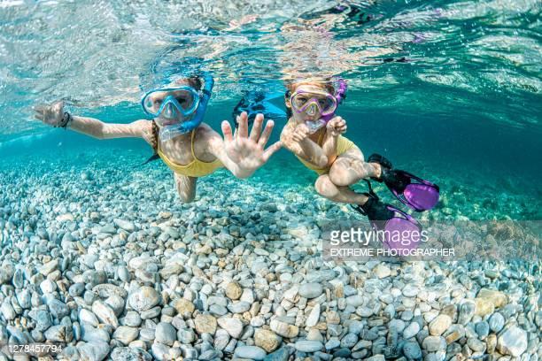 2人の女の子が旅行先で水中を楽しむ - スクーバダイビングの視点 ストックフォトと画像