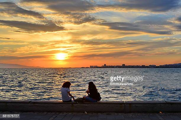 two girls enjoying sunset at izmir bay - emreturanphoto stock-fotos und bilder