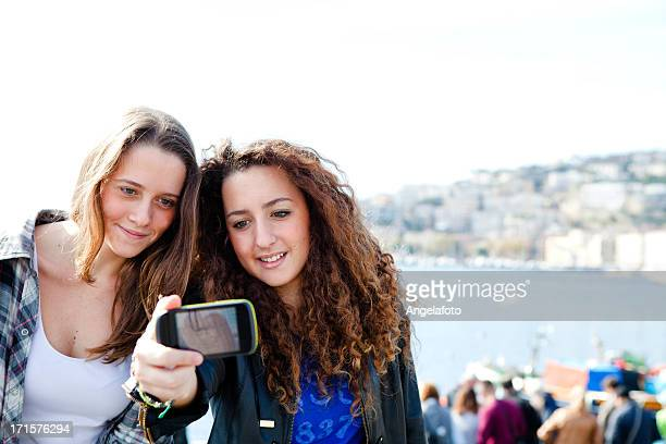 Two girls enjoying with a smartphone in Naples