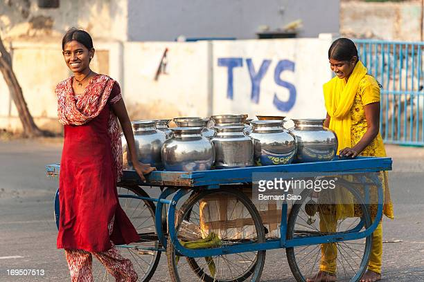 Two girls fetch potable water using water jugs and a push cart Hyderabad, India, 2008
