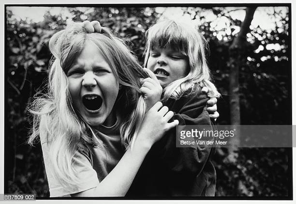 two girls (9-11) fighting outdoors (b&w) - girl wrestling stock pictures, royalty-free photos & images