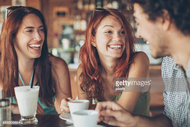 Two girls flirting with a man in the bar