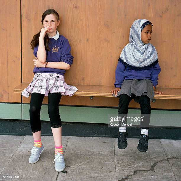 Two girls from different ethnic backgrounds pause for a moment during playtime at Kingsmead Primary School which serves children who live on the...