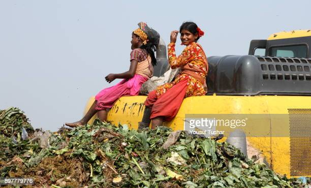 Two girls from indigent community taking rest on bulldozer at garbage pile in Matual dumping yard They collect usable things that are sold to make...