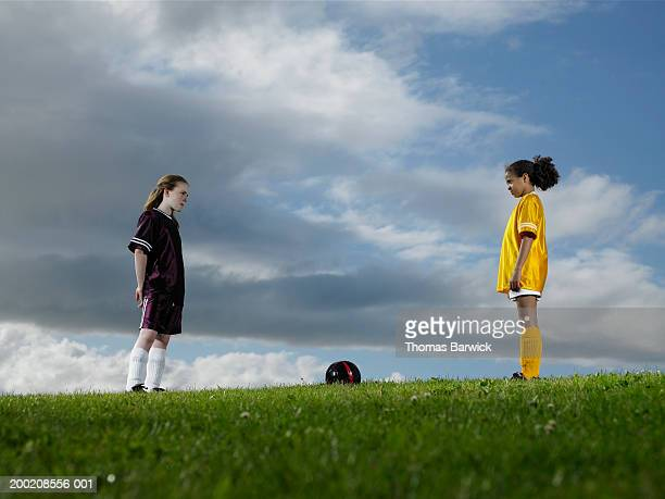 Two girls (9-11) from opposing soccer teams staring at one another