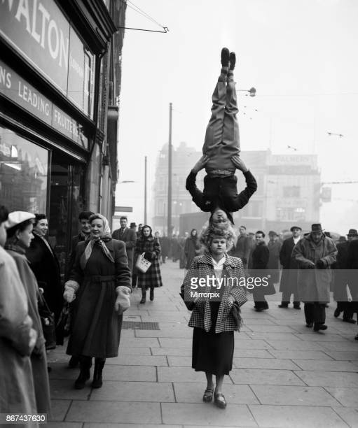 Two girls from the Chaludis act perform in the street at Hammersmith, London, 13th January 1953.
