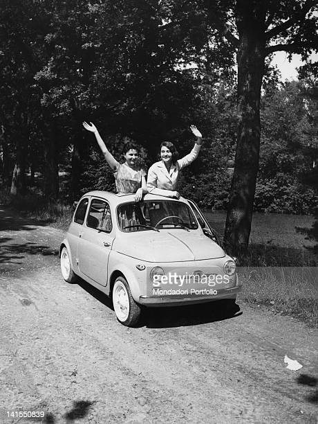 Two girls greeting from the opened sunroof of a car Fiat 500 stationary in a country road Italy June 1957