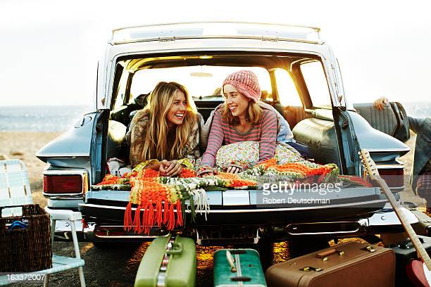 Two girls hanging out in a car at the beach.