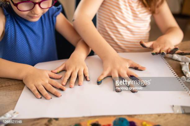 two girls having fun while finger painting together at home - 4 girls finger painting stock pictures, royalty-free photos & images