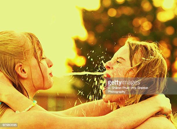 Two Girls Having Happy Water Fight Fun Together