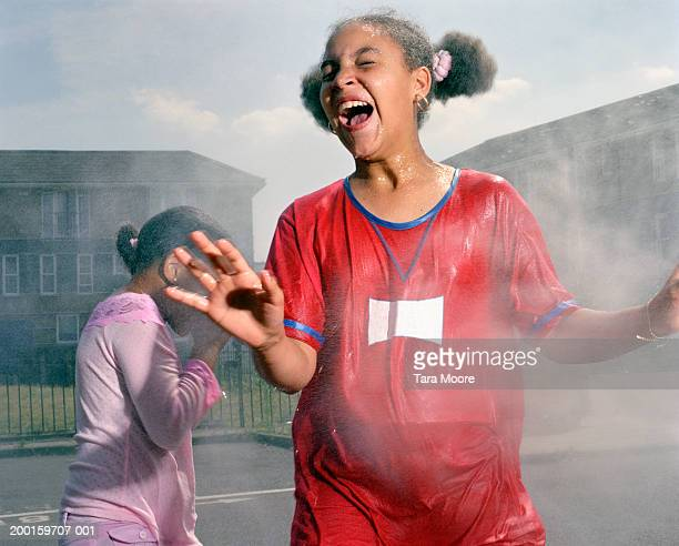 two girls (9-11) having water fight in street - wet t shirt girls stock photos and pictures