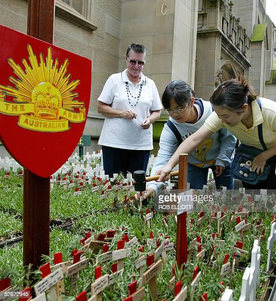 """Two girls help each other as they hammer in a small wooden cross in a """"field of remembrance"""" in Sydney, 21 April 2005, watched on my a representative..."""