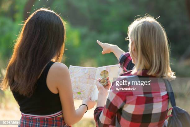 two girls hiking in forest and using compass - geografia fisica foto e immagini stock