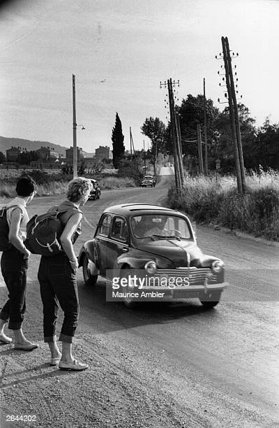 Two girls hitchhiking by the roadside Original Publication Picture Post 7226 We HitchHiked To the Sun On 5 pub 1954