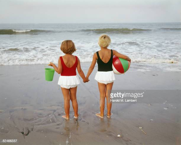 Two young girls, in similar bathing costumes, hold hands as they stare out into the surf, one with a beach ball under her arm and the other with a...