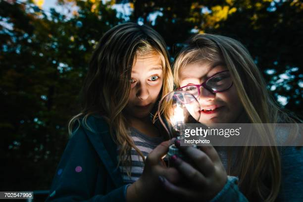 Two girls holding and staring at illuminated lightbulb in garden at dusk