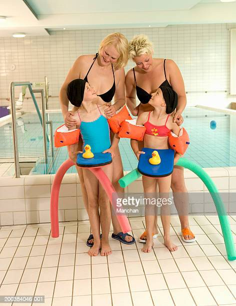 Two girls (8-10) holding floats with mothers by swimming pool