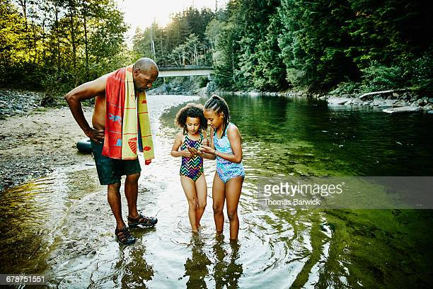 Two girls holding frog while father looks on