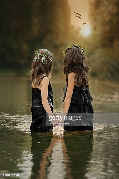 Two girls (8-9, 10-11) holding hands and watching sunset