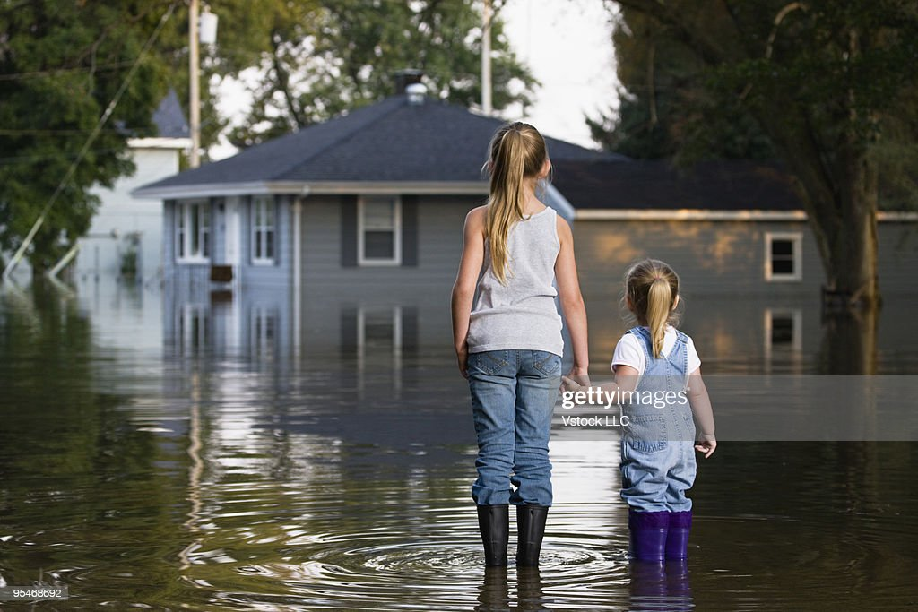 Two girls holding hands, watching during flood : Stock Photo