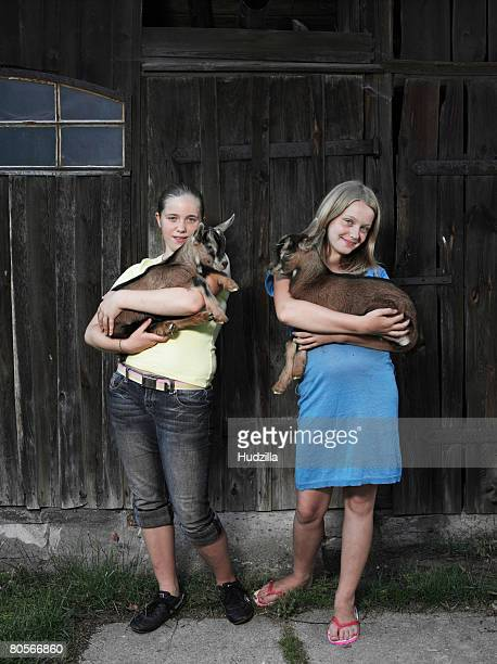 two girls holding kid goats - girl wear jeans and flip flops stock photos and pictures