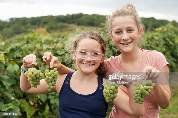 Two girls holding Niagara grapes in an orchard