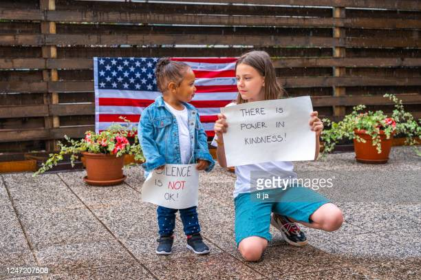 two girls holding posters with anti-racist messages outdoors in the rain - anti racism stock pictures, royalty-free photos & images