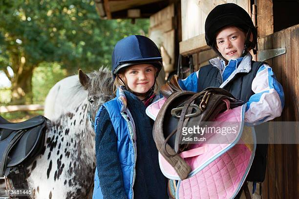 Two girls holding saddles with pony