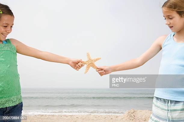 Two girls (9-11) holding starfish on beach