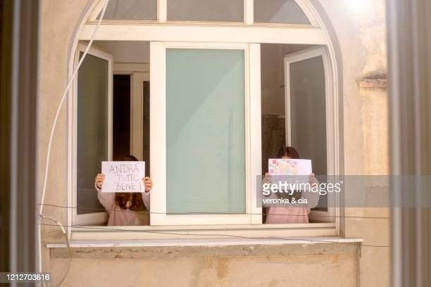 two girls holding up postres in italian - italy coronavirus stock pictures, royalty-free photos & images