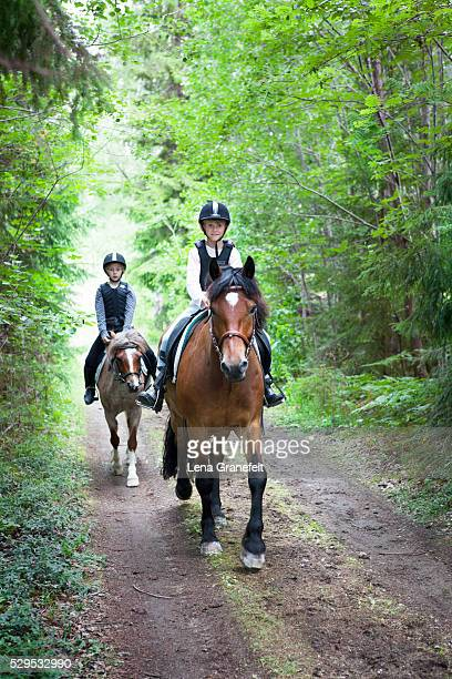 Two girls horseback riding on rural road